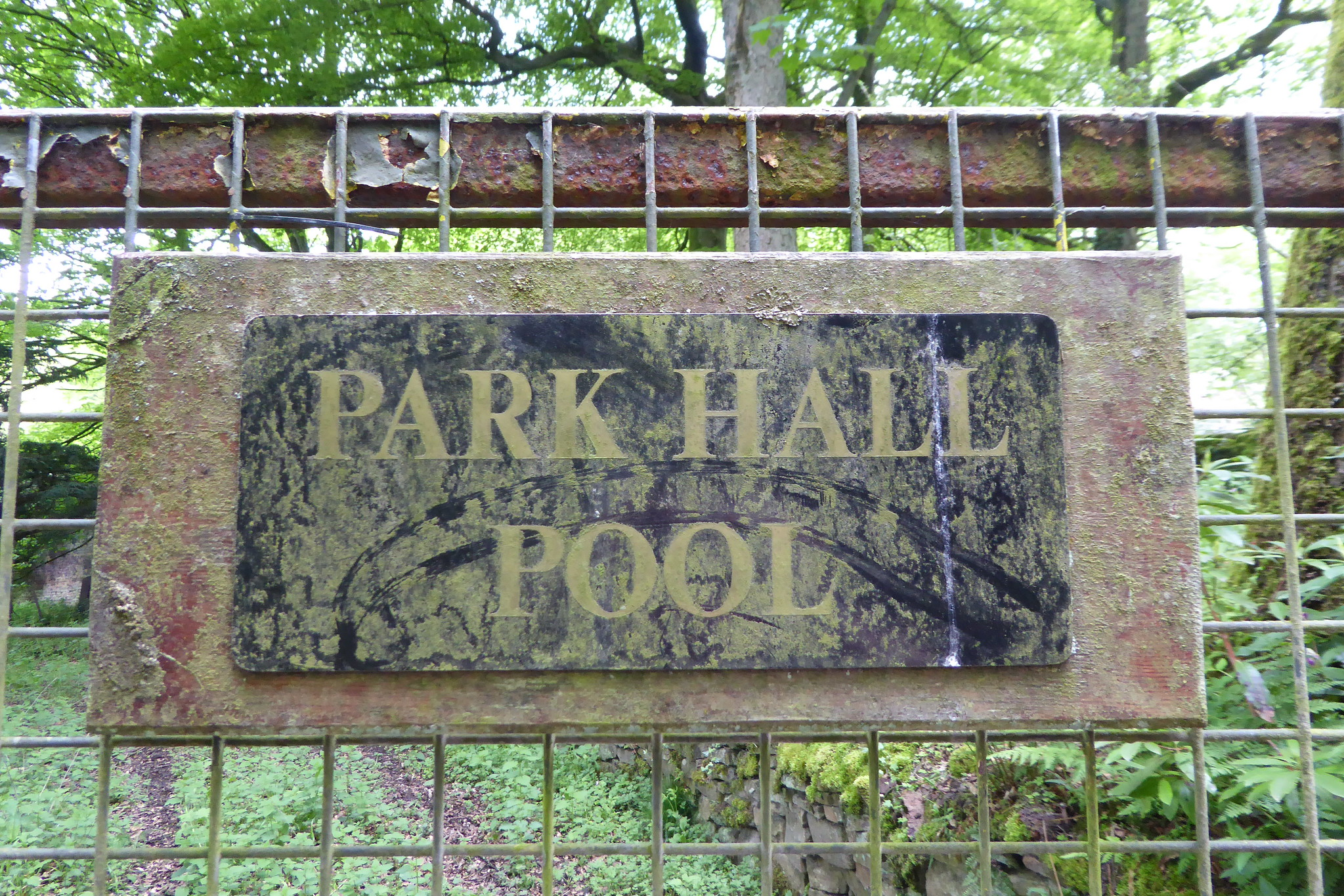 An old faded sign for Park Hall Pool